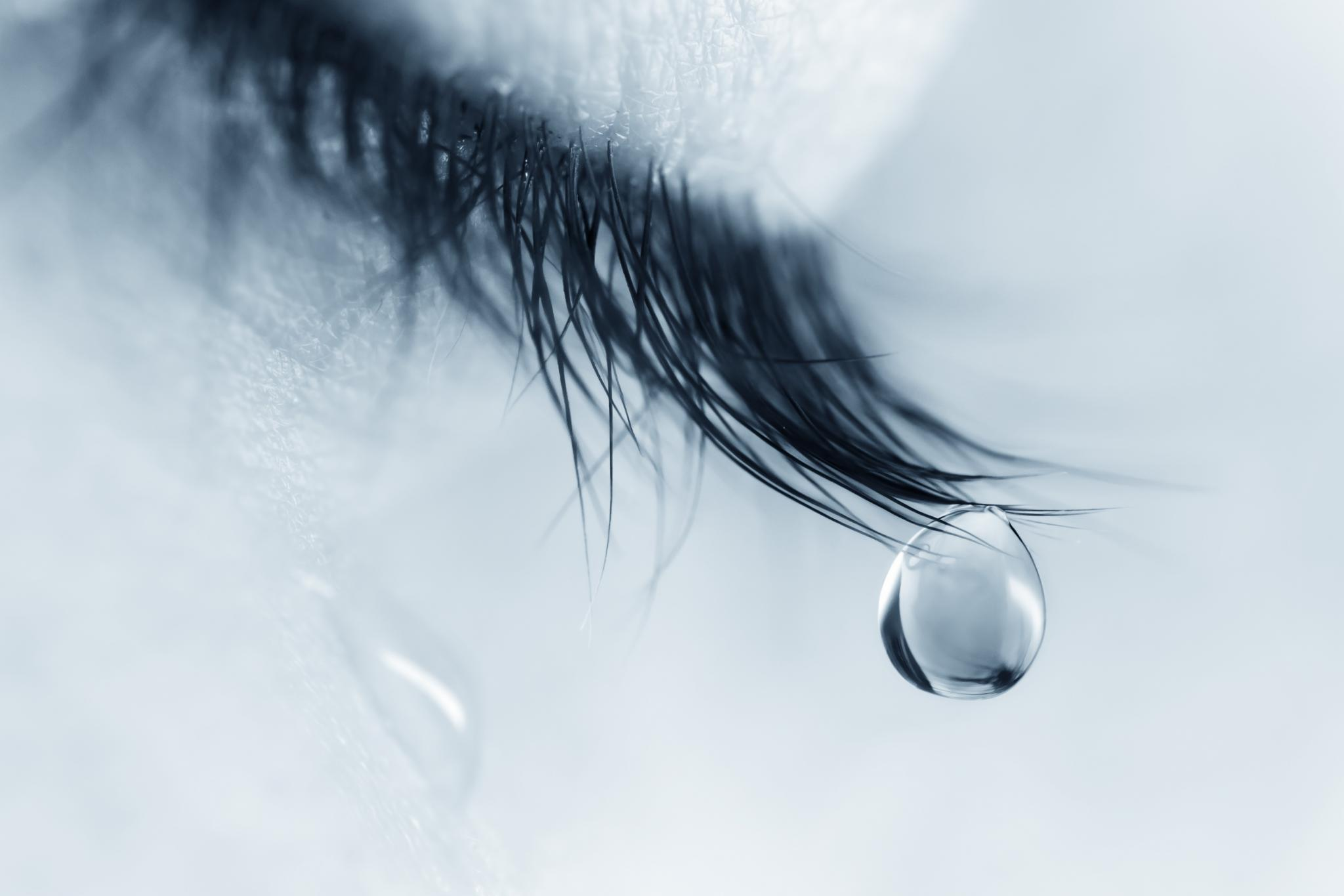 Eye with a single tear drop.