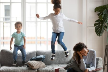 Busy mom with kids jumping on couch.